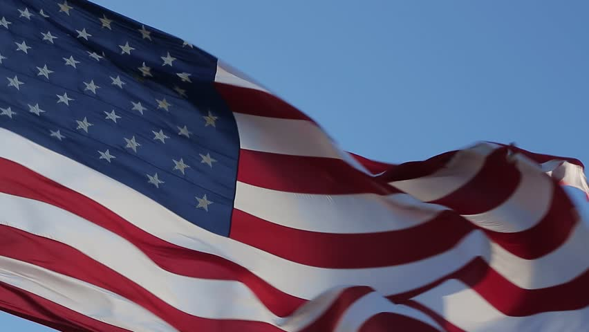 American flag is flying in the wind on a sunny day. Symbol of the Amenrican national holiday. Shooting close-up. Independence Day - American concept. Waving United states of America famous flag.