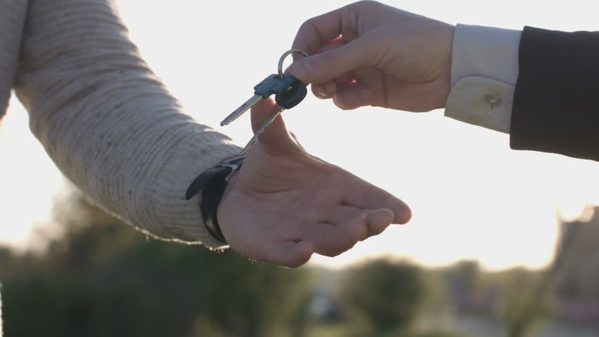 Hand of businessman giving keys to client. Two men shaking hands on nature background. Close up. Oudoor.