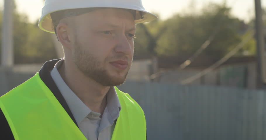 Portrait of serious caucasian builder in a green vest going at initial stage of construction. Outdoor. | Shutterstock HD Video #27672235