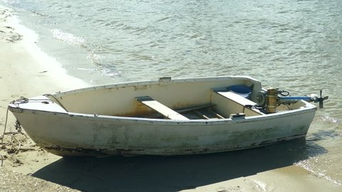 Old dilapidated wooden dinghy with old Seagull outboard motor.