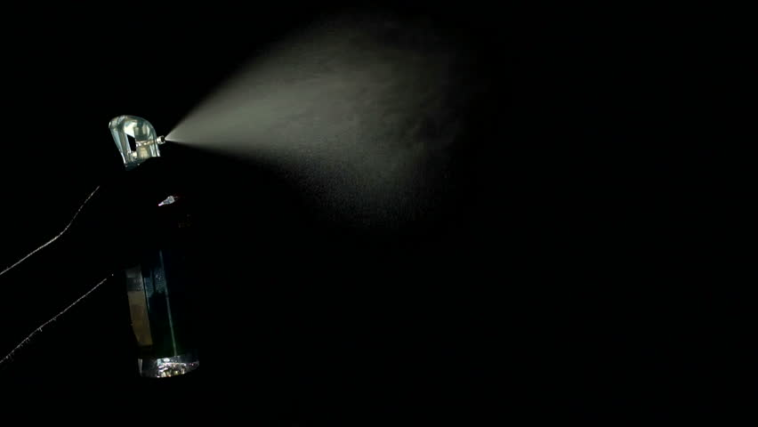 Close-up of woman's hand spraying an aerosol in the dark on a black background. Slow motion.