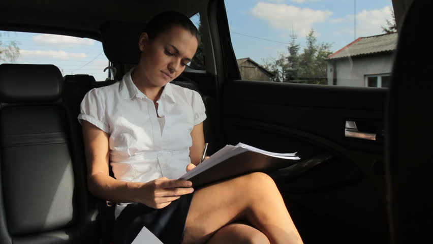Beautiful businesswoman viewing documents on the back seats of car
