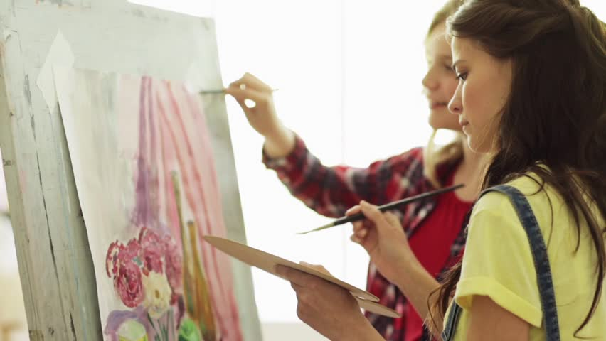 art school, creativity and people concept - student girls or friends with easel, paintbrushes and palettes painting still life at studio #27710722