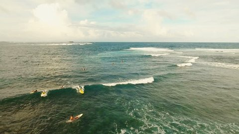 Surfers at siargao islands famous surf break cloud 9 near mindanao the Philippines. Aerial view :People learning to surf at Cloud nine surfpoint in Siargao, Philippines.