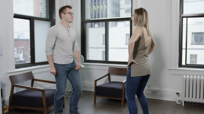 Young hip urban professionals dancing in white bright lofty living room of city apartment | Shutterstock HD Video #27725044