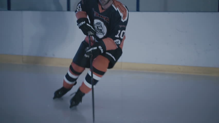 Hockey player hits the puck with a stick on ice close-up