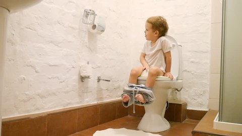 A little baby boy being potty trained uses the toilet