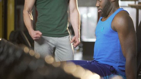 Personal trainer actively motivating young man during dumbbell exercise in gym