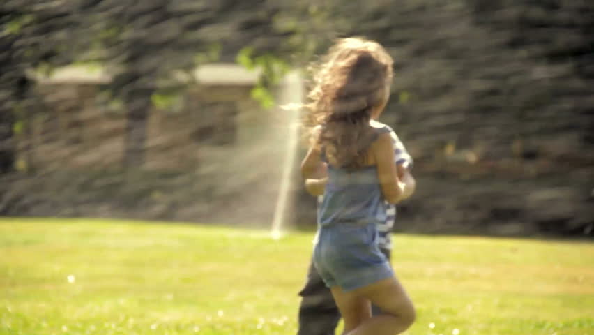 Kids are playing in a park with sprinklers