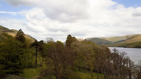 Ullswater, English Lake District. Aerial drone video footage rising from a countryside forest to reveal the lake of Ullswater and its surrounding hills in the heart of the English Lake District.