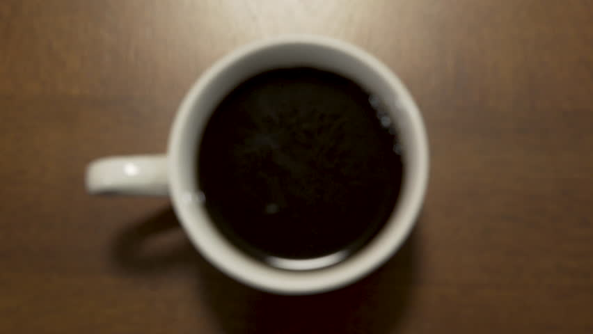 Rack Focus to Coffee Cup Being Picked Up