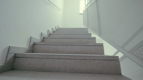 Climbing the white stairs. Someone step by step climbs the steps POV. Climb up the stairs, passing one floor after another in the hotel. Modern interior, white walls, stairs are covered with tiles