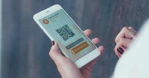 Caucasian female making a payment with bitcoins cryptocurrency using her smartphone. Custom application interface design. 4K UHD RAW edited footage