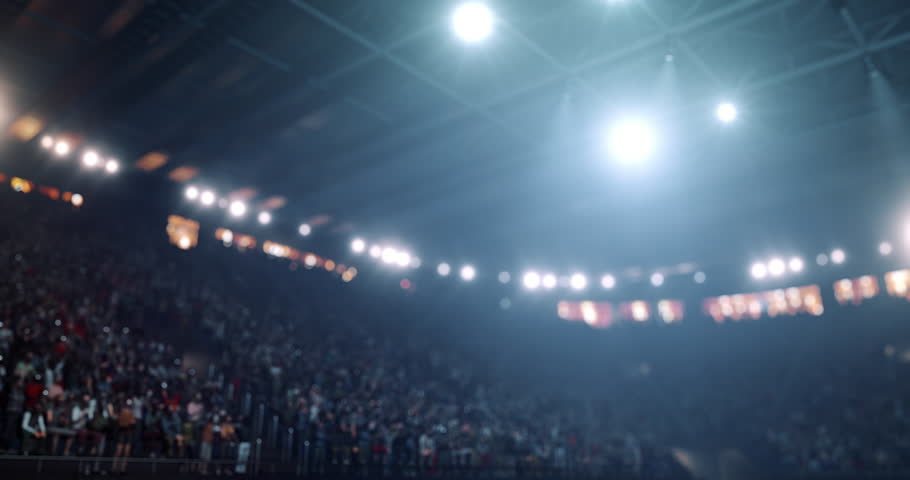 4k video footage of an indoor floodlit basketball arena full of spectators.