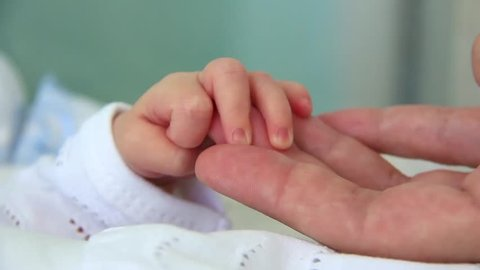Hand in hand. Mother and newborn daughter in maternity hospital