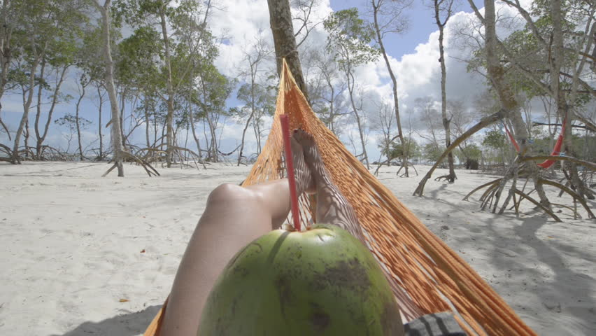 First person view of beautiful girl drinking coconuts milk laying on a hammock in a mangrove forest in Jericoacoara, Brazil