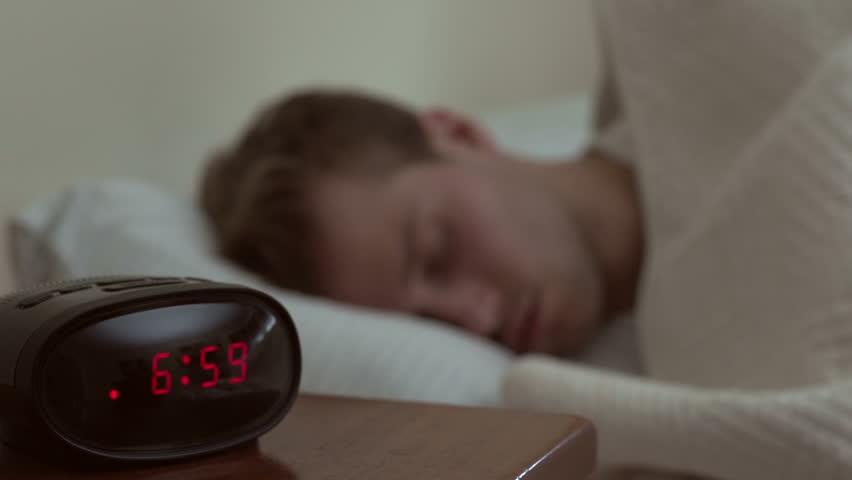 Man waking up to his alarm