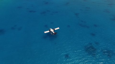 Aerial view of tropical landscape seaplane parking at sea close to coral reef maldives island