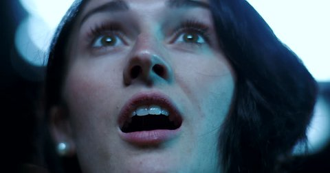 Low angle of a surprised look on a young woman's face as she watches a movie at the cinema