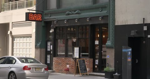 A daytime exterior establishing shot of a bar and restaurant in downtown Manhattan, New York City.  Day/Night matching available.