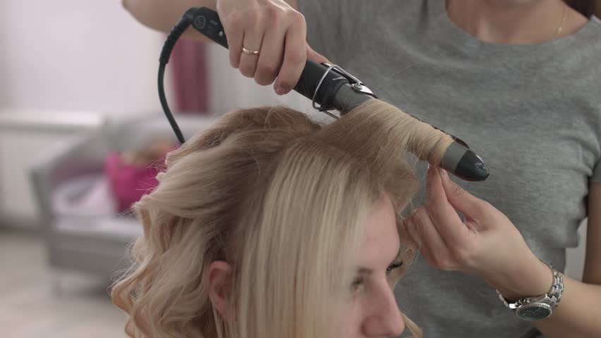 Hair stylist makes a curls for a girl, using hair styling. Hairdresser at work. | Shutterstock HD Video #27852625