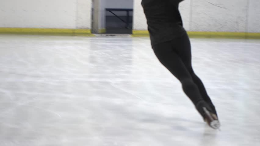 Female ice figure skating, closeup on feet, spinning, low angle, slow motion HD video