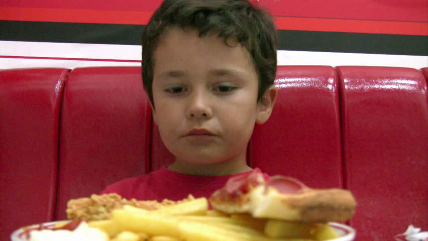 Little boy eating pizza and fries