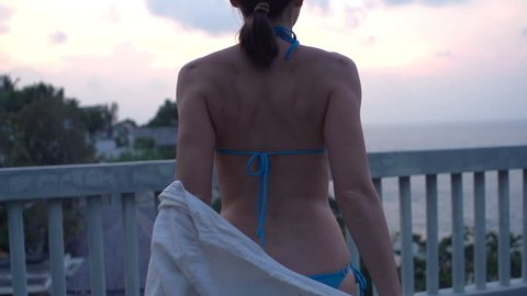 Sexy woman taking off shirt on terrace during sunset, super slow motion 240fps