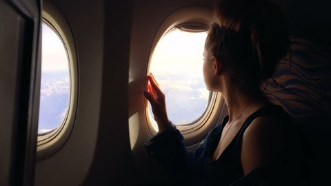 A young girl travels by plane and sits by the window and enjoys the view and then closes the porthole. 1080p