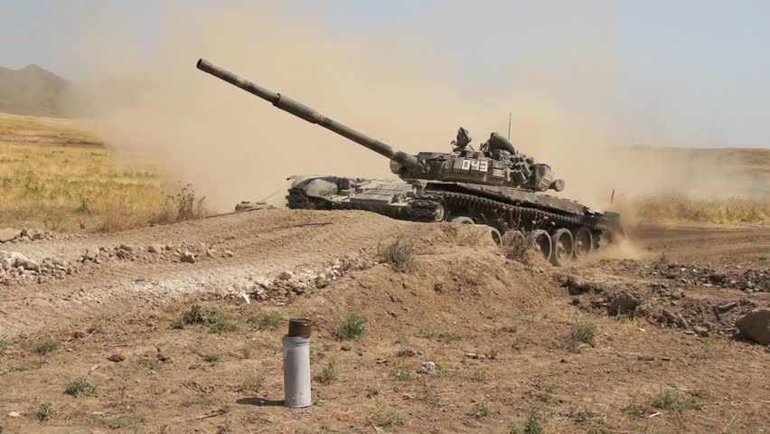 Tank-T72 on the test site in the desert area overcomes a long line in its path and slowly climbs on the edge picking up a column of dust behind you. The video was filmed by a  military videographer.