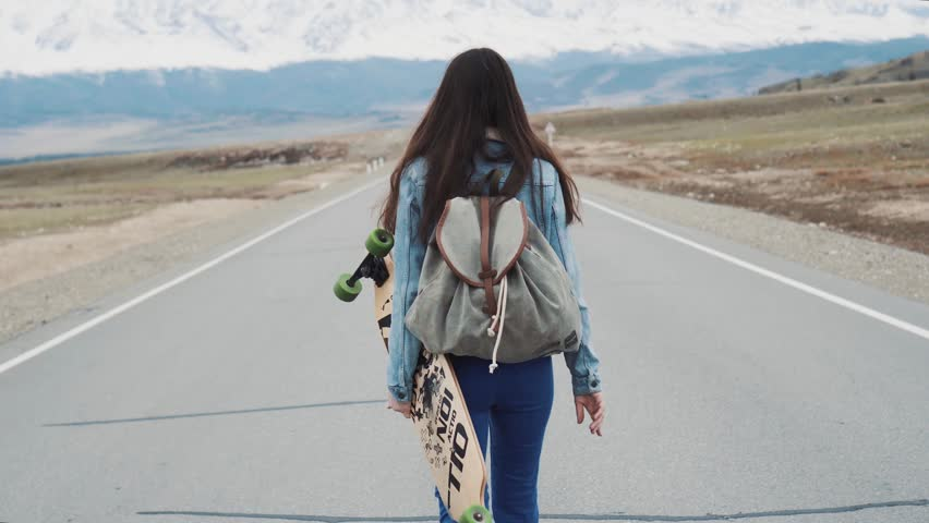 Young girl teenage hipster walks on highway with longboard. With a camp backpack and a jersey jacket. Against the backdrop of snowy mountains. The girl is traveling alone. | Shutterstock HD Video #27926905