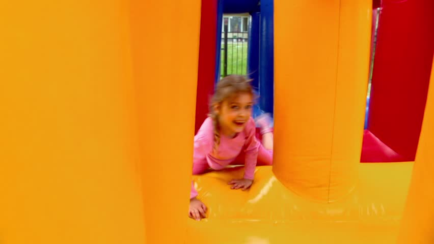 Two kids boy and little girl crawls at inflatable playground at sunny summer day