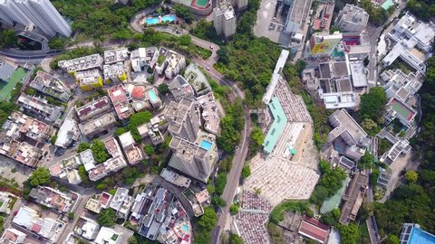 Tilt pan aerial shot over Sandy Bay area at Hong Kong island western district. Victoria Gardens tower straight under the camera, low section of Chinese Christian Churches Union cemetery beside
