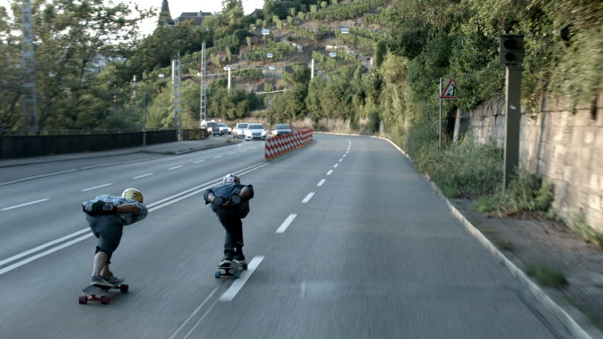 Pair of skateboarders speed down a street in Stuttgart. As cars drive by on the opposing street lane. Tracking shot.
