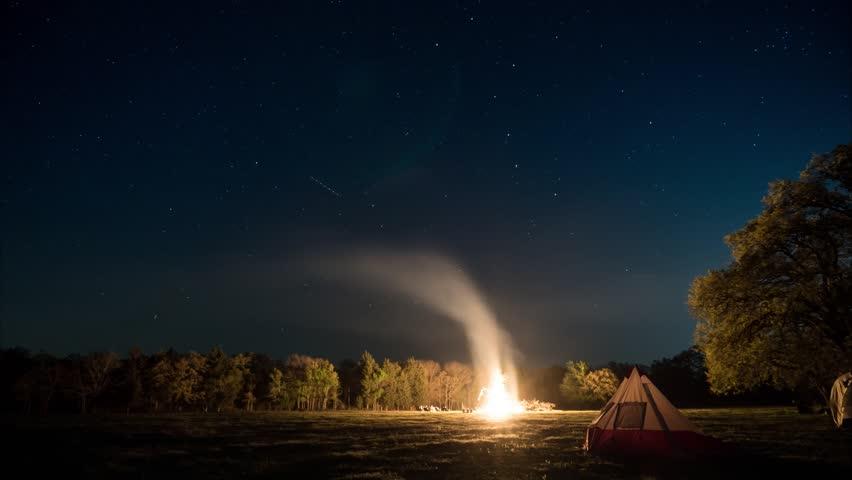 Night sky timelapse as a bonfire party ensues near camp down below.