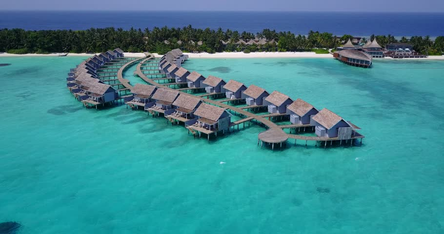 v03684 Aerial flying drone view of Maldives white sandy beach on sunny tropical paradise island with aqua blue sky sea water ocean 4k luxury 5 star resort hotel water bungalow hut relaxing holiday