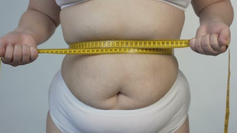 Body hatred, corpulent woman measuring her belly and tightening tape-line, diet