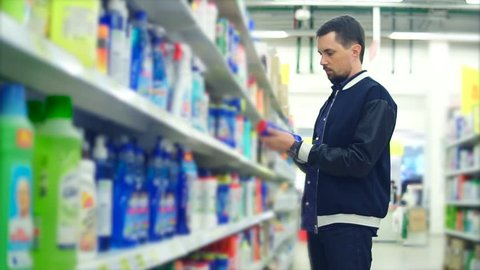 A middle-aged man chooses a means with bleach to clean his apartment, on the shelves in the giermarket there is a lot of goods for cleaning the bathroom, people are holding a blue jar