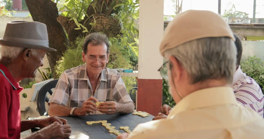 Happy active retired people, old hispanic friends and free time, senior men having fun and playing game of domino at home.
