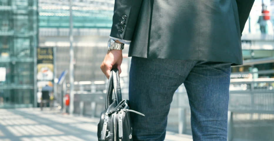 A young handsome businessman (student) in a suit, comes with a briefcase, at the station, airport. Concept: a new business, traveling the world, communication, contacts, a new deal, success, walk.