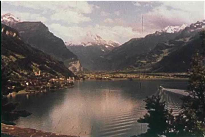 1950s: Footage of the Swiss Alps is shown, then a young man plays an accordion at a picnic in a warmer locale in 1959.