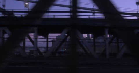 A passenger's side view background plate looking out the window of a subway car as it passes over the Manhattan Bridge. The New York City skyline at dusk is seen in the distance.