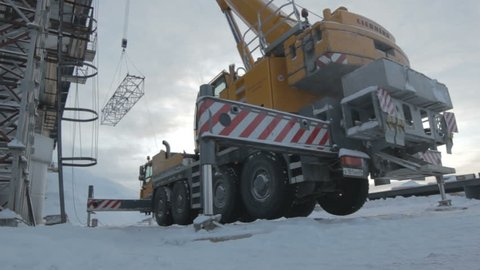 SALEHARD, YAMAL-NENETS/RUSSIA - JUNE 15 2012: Bottom view modern large yellow crane truck stands on supports in snow and transports metal beam on June 15 in Salehard
