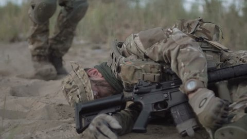 Slow motion the soldier saves getting injured while shooting and having contact on battlefield.