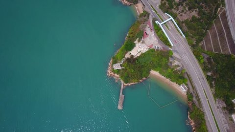 Fly over Castle Peak Road along shore, camera tilt up from top-down view, reveal aerial view at Sham Tseng district and channel panorama. Airport Core Programme Exhibition Centre placed on small cape