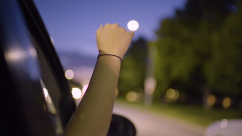 Young Woman Puts Her Hand Out Car Window To Feel The Breeze, At Night, On Tree Lined Street In City