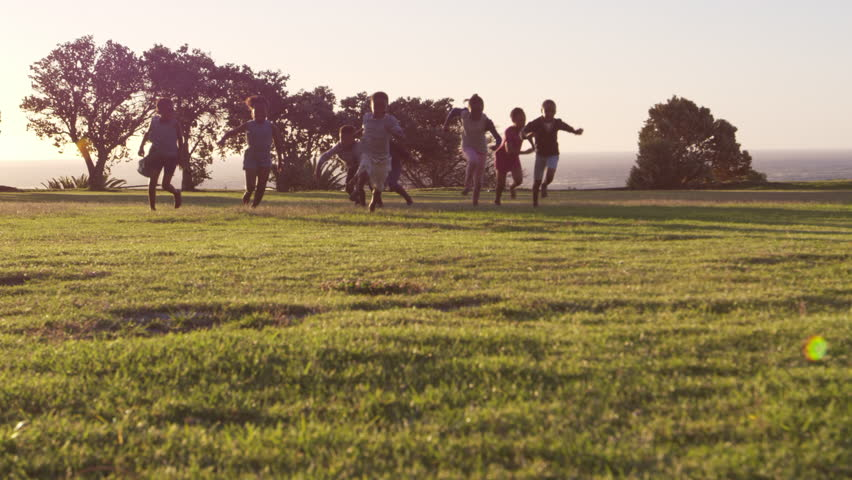 Elementary school kids playing with a football in a field