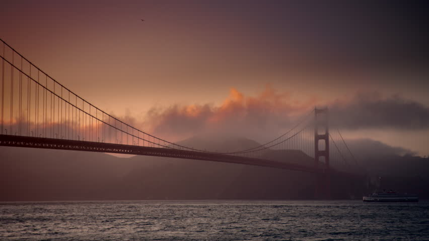 Ferry boat going under Golden Gate Bridge in San Francisco California in 4K at sunset with dramatic clouds