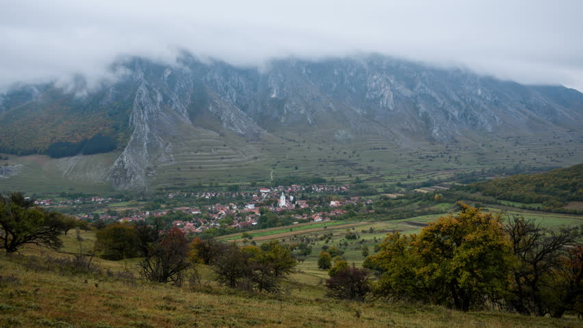 Panorama of Rimetea village in Transylvania, Romania. Rimetea, a remote Transylvanian mountain village, in autumn. 4k time lapse of clouds over Piatra Secuiului Mountain.