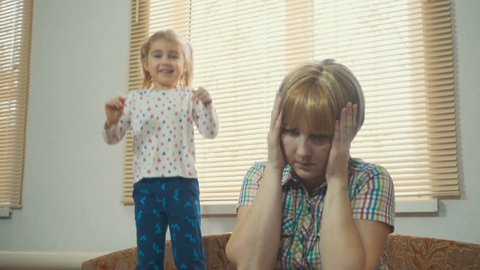 Cute little girl jumping on the bed. Mother calms unruly child. A hyperactive kids. Preschool Education.